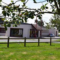 Vue de la Boutique Jacky Leduc derrière les pommiers lors d'une journée ensoleillée.